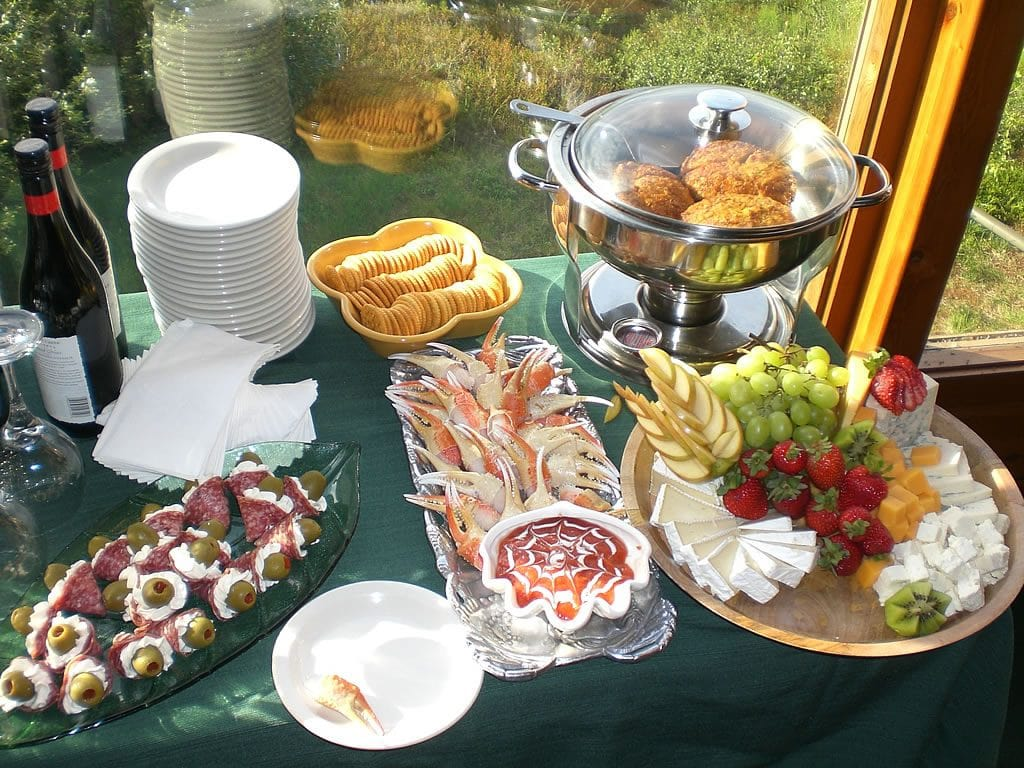 Large spread of food with crab legs, an assortment of cheeses, and more!