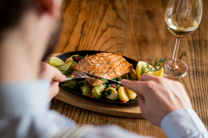 man eating salmon with white wine